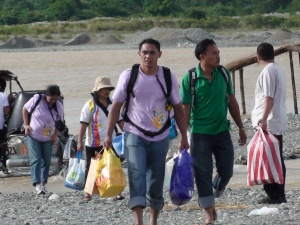 Cesar, Sir Charlie, Ma'am Flor, Manang Josie and the others, with bags and all other things in tow cross the river on the brage.